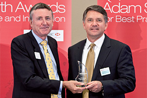 Bank Relationship Management, Winner – Photo of Richard Parkinson and John J. Tus from Honeywell accepting on behalf of Jim Colby.